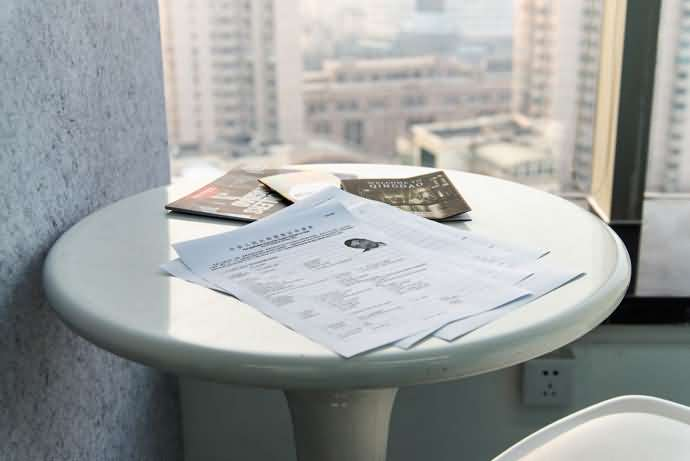 "Visa application form, ""welcome to qingdao"" map, and small magazines, on a clean white table in the XMandarin study area. City afternoon outside the window"