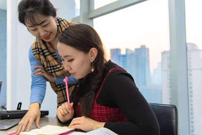 Chinese teacher is smiling and explaining some problem to her student who is looking a bit troubled, while in the background the sun is going down