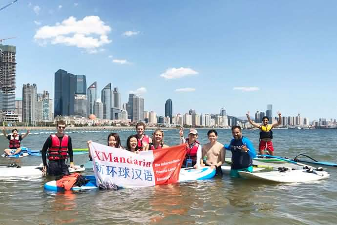 Chinese language students and teacher holding the XMandarin flag during a summer monthly water playing event, standing in the water by the beach with the skyscrapers of Qingdao in the background